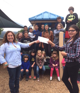 Papermill Creek Children's Corner director Lourdes Romo receives the grant from the 8th grade class!